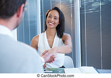 Female executive shaking hands with man