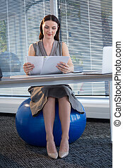 Female executive sitting on exercise ball while reading documents at desk