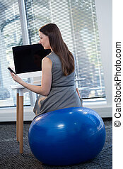 Female executive sitting on exercise ball while working at desk