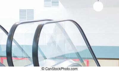 Female executive taking the escalator.