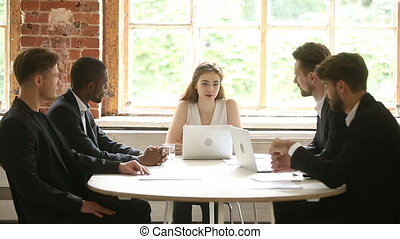 Female executive talking to diverse male employees at office meeting