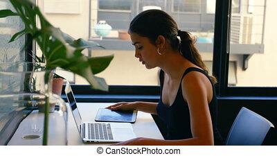 Female executive using laptop at desk 4k - Female executive...