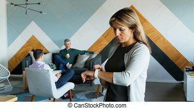 Female executive using smartwatch 4k - Female executive...