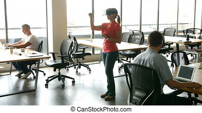 Female executive using virtual realty headset while her...