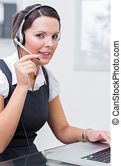 Female executive wearing headset while using laptop at desk