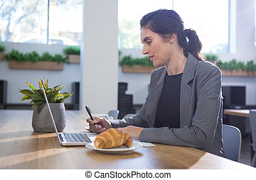 Female executive working at desk while having breakfast