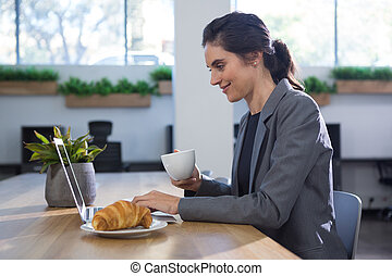 Female executive working at desk while having coffee at table