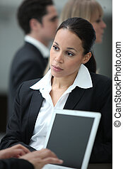 Female executive working with colleague at a laptop