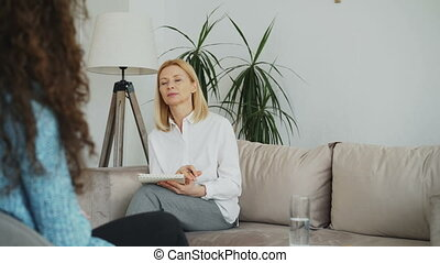 Female experienced psychologist talking and listening to upset woman patient and writing notes on clipboard in her office indoors