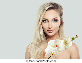 Female face. Beautiful blonde woman with healthy skin, wavy hair and white orchid flowers on banner background