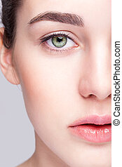 Closeup shot of female face with day makeup and green pistachio colour eyes