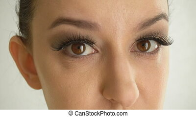 Female face with long false eyelashes and brown eyes looks...