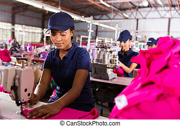 female factory worker sewing with colleagues on background