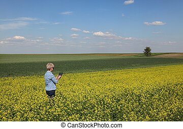 Female farmer examining blossoming rapeseed field in spring