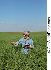 Female farmer inspecting rapeseed crop in field