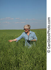Female farmer inspecting rapeseed crop in field using tablet