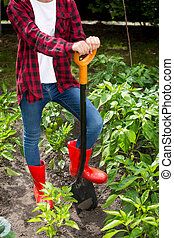 Female farmer posing with shovel on garden bed at sunny day