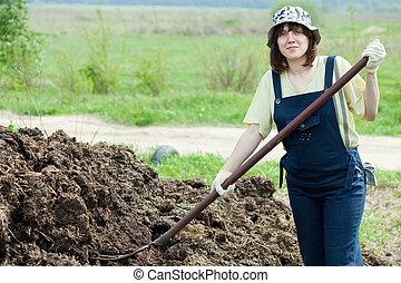 Female farmer spreads manure at farm