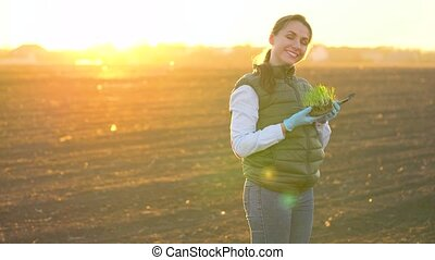 Female farmer stands with a sample of seedlings in her hand...
