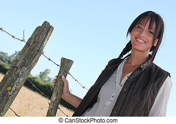 Female farmer stood by barb-wire