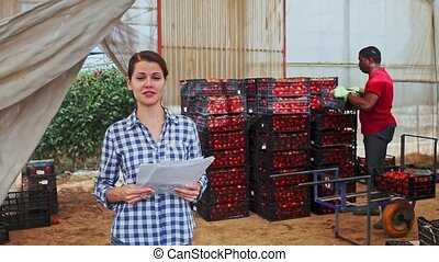 Female farmer working with papers in warehouse, afro male ...