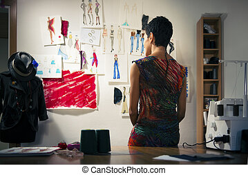 Female fashion designer contemplating drawings in studio - ...