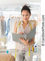 Female fashion designer looking at folder