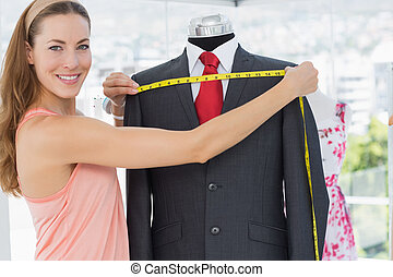 Female fashion designer measuring suit on dummy - Portrait ...