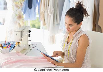 Female fashion designer using digital tablet in studio -...