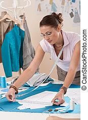 Female fashion designer working at studio