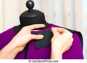 Female fashion designer working on mannequin.