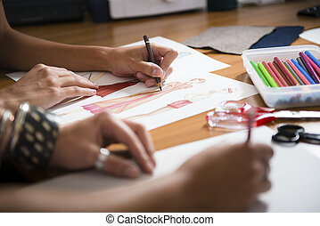 female fashion designers drawing new dress in studio - two ...