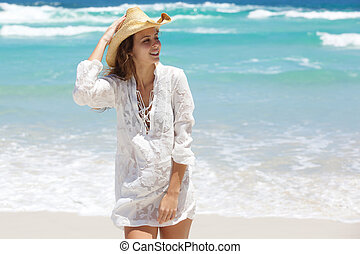 Female fashion model in white summer dress and hat