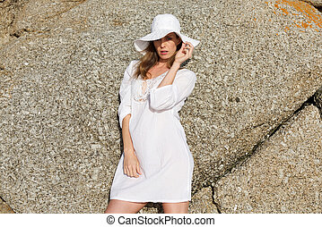 Female fashion model in white sun dress and hat