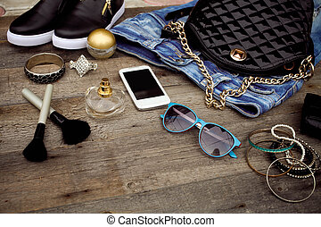 Female fashionable accessories on a wooden background.