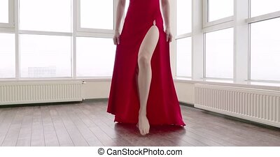 Female feet. A beautiful woman in a long red dress with a slit is following you. Sensual video. Temptation