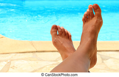 Female feet by the poolside blue waters