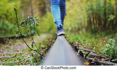 Female feet carefree walks along railway. Girl goes on rails...