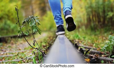 Female feet carefree walks along railway.
