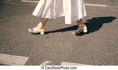 Female feet cross the road