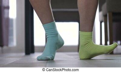 Female feet dancing in mismatched socks
