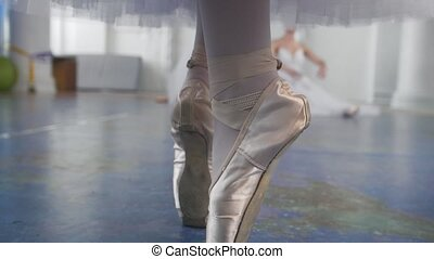 Female feet dancing in pointe shoes in front of ballerinas...