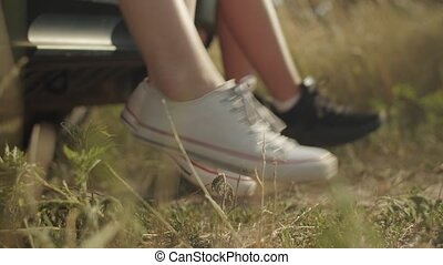 Close-up female feet dangling from car trunk on sunny day during road trip in countryside. Women's legs in sneakers hanging from open car trunk while travelers relaxing on summer vacations car trip.