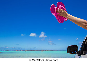 Female feet from the window of a car on a background of tropical beach
