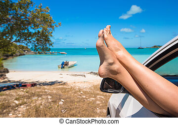 Female feet from the window of a car on background tropical beach