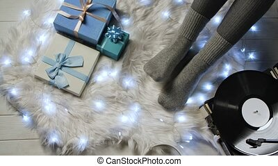 Female feet in gray socks next to blue gift boxes, headphones, luminous garland and retro turntable vinyl. Woman relaxes on white fur. Home comfort concept. Expectation of the winter holidays Christmas and New Year. Close up. Slow motion.