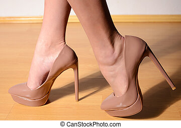 Female feet in light-brown high-heeled shoes on the wooden floor