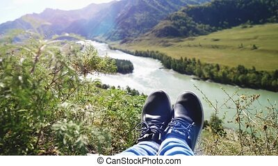 Female feet in running shoes sitting on top of mountain with amazing landscape on mountains river and beautiful sun flare effect. Slow motion,