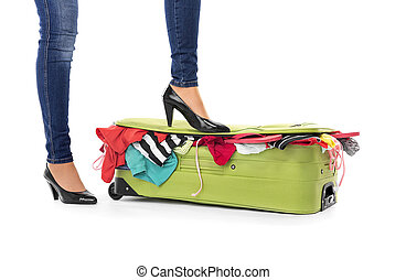 Female feet in shoes on a suitcase.