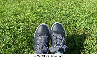 Female feet in sneakers gumshoes on a sunlit green grass, close up. High quality 4k footage.